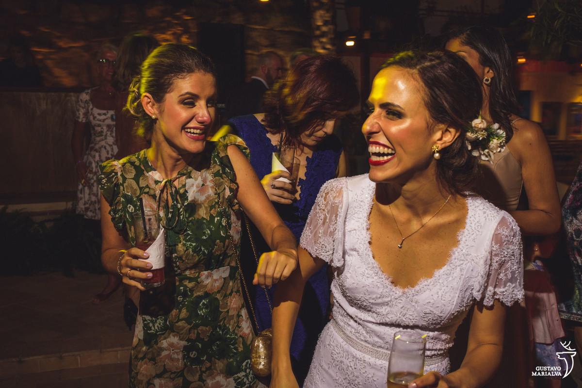 noiva dança com amiga segurando taça de espumante e sorrindo