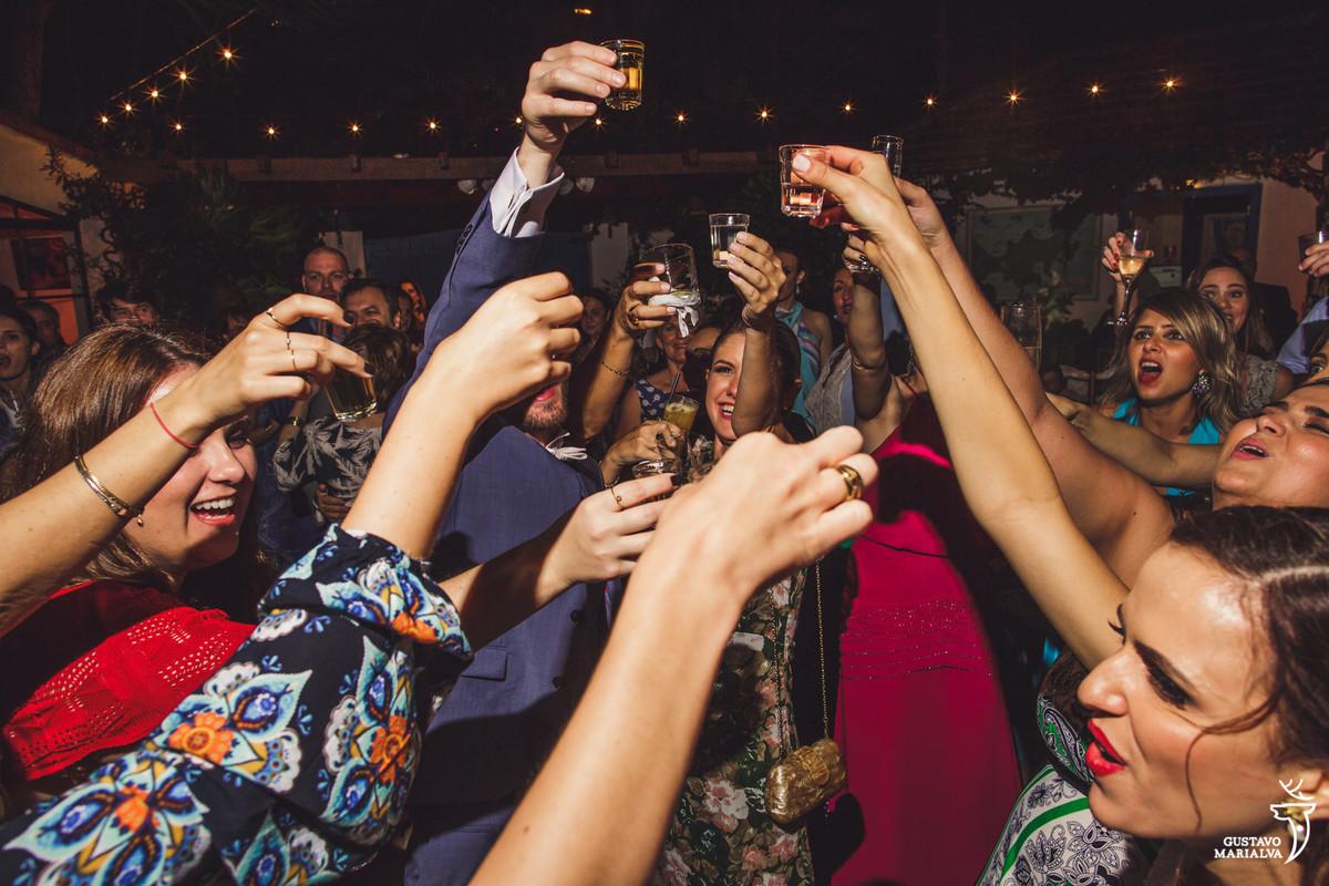 noivos e convidados fazem brinde com shots de cachaça