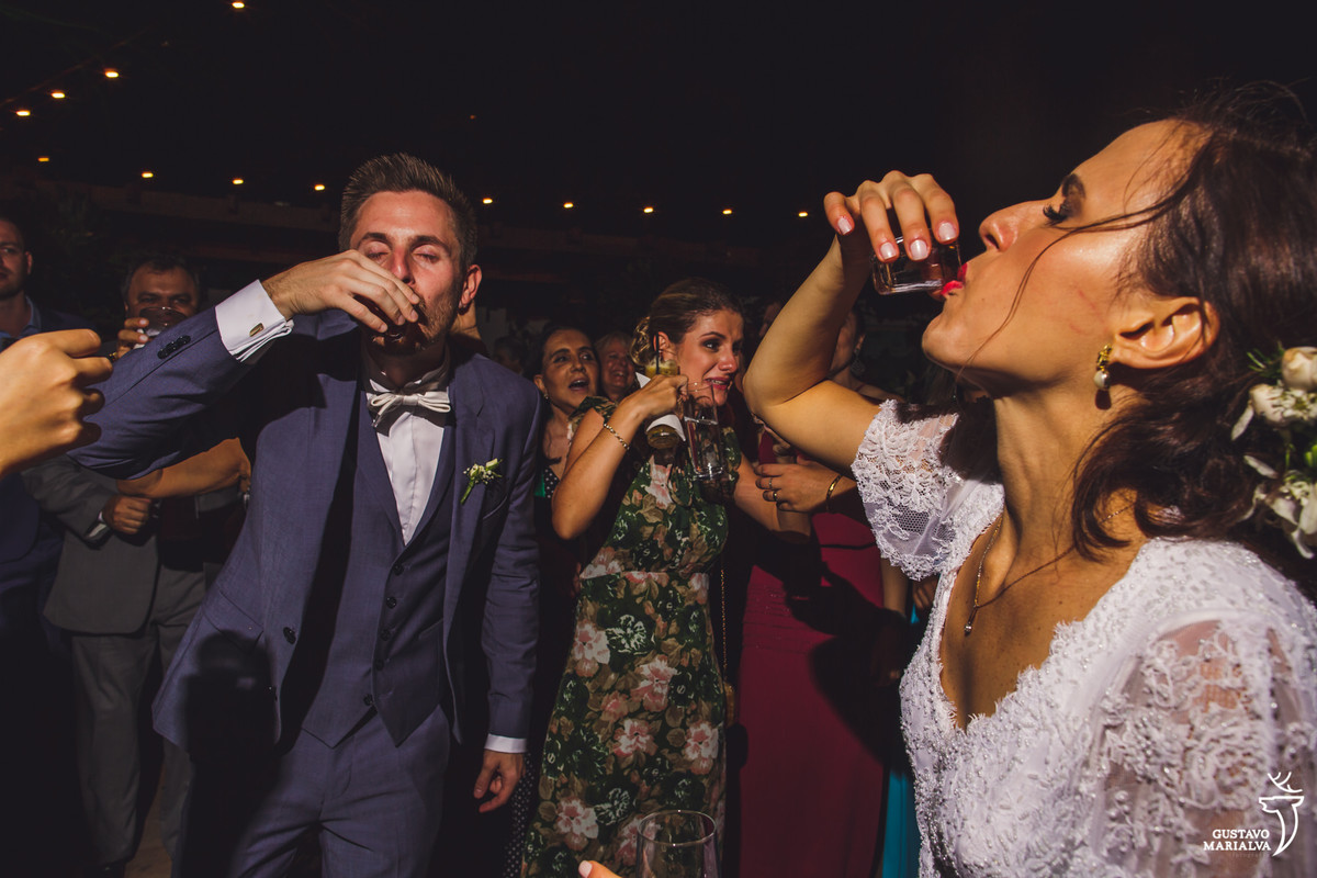 noivos tomam shot de cachaça enquanto convidada faz careta ao fundo