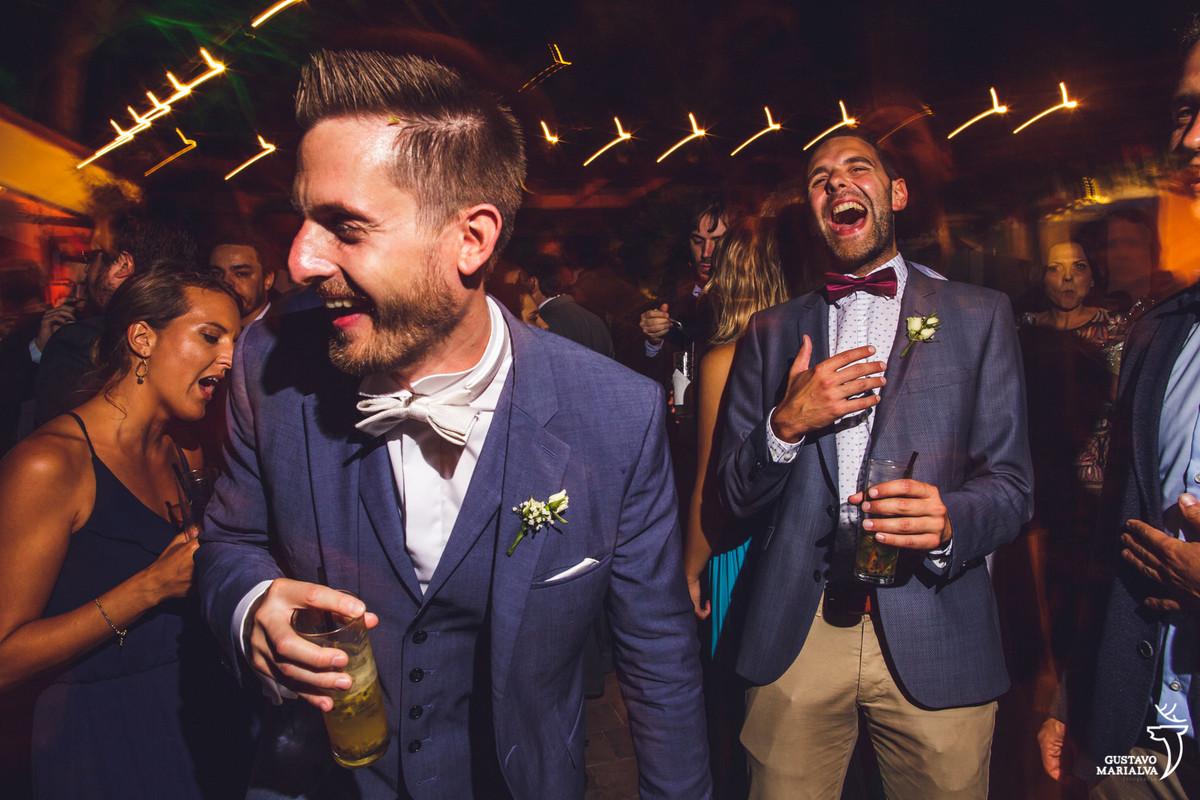 noivo dança sorrindo com o copo na mão enquanto amigo sorri ao fundo