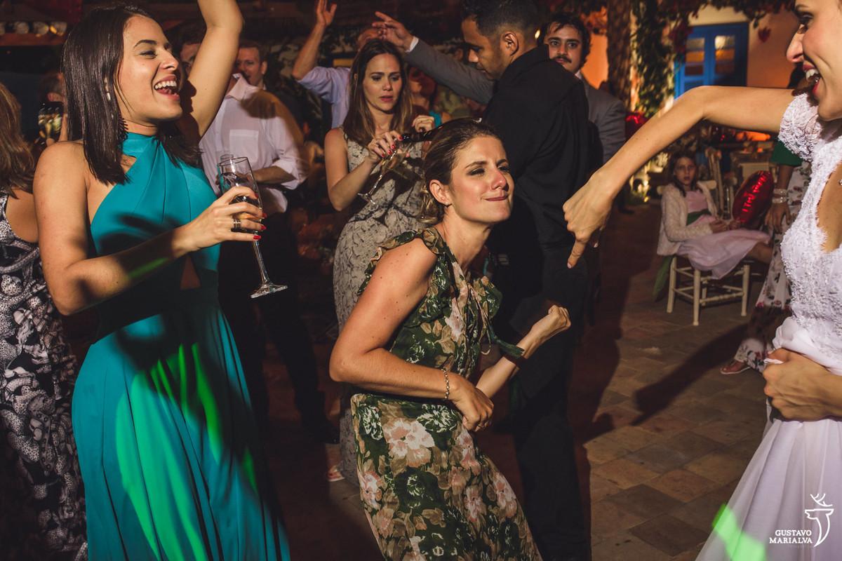 convidada faz air guitar e dança animada enquanto amiga pula com taça de espumante nas mãos