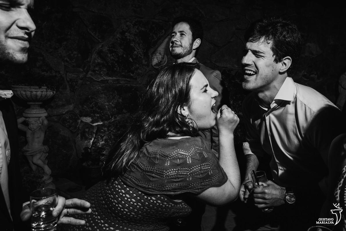 amigos cantam simulando o microfone com as mãos enquanto homem faz careta ao fundo