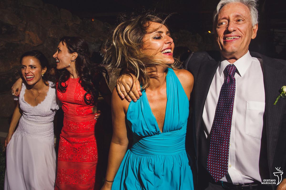 pai da noiva e convidada dançam abraçados enquanto noiva e irmã se abraçam no fundo