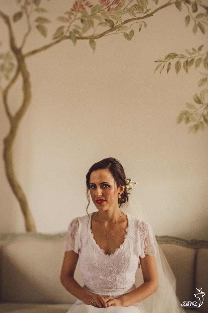 noiva sentada no sofá posando para retrato com árvore pintada na parede ao fundo no hotel vila da santa em búzios