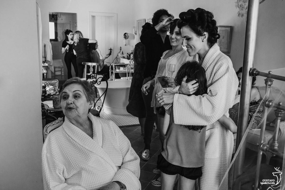 noiva abraça a sobrinha enquanto a avó manda um beijo sendo observada pela neta durante o making of do asamento