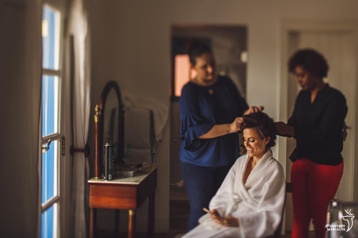 noiva arruma o cabelo sorrindo durante o making of do casamento no hotel vila da santa em búzios