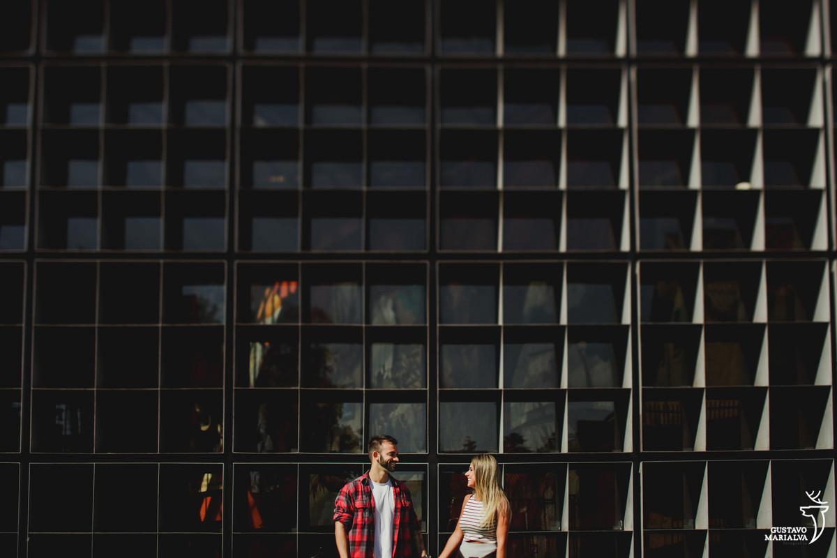 homem de camisa xadrez e mulher de camisa listrada posam para book de casal no largo da ordem em curitiba