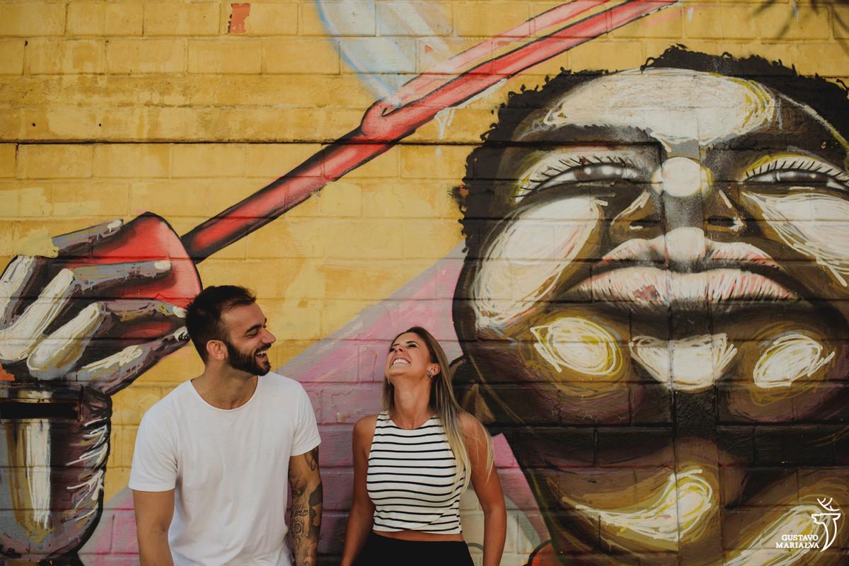 casal sorri olhando para cima com grafite desenhado na parede no largo da ordem em curitiba