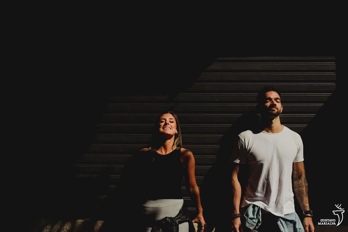 casal posa olhando com o rosto para cima em frente a portão cinza