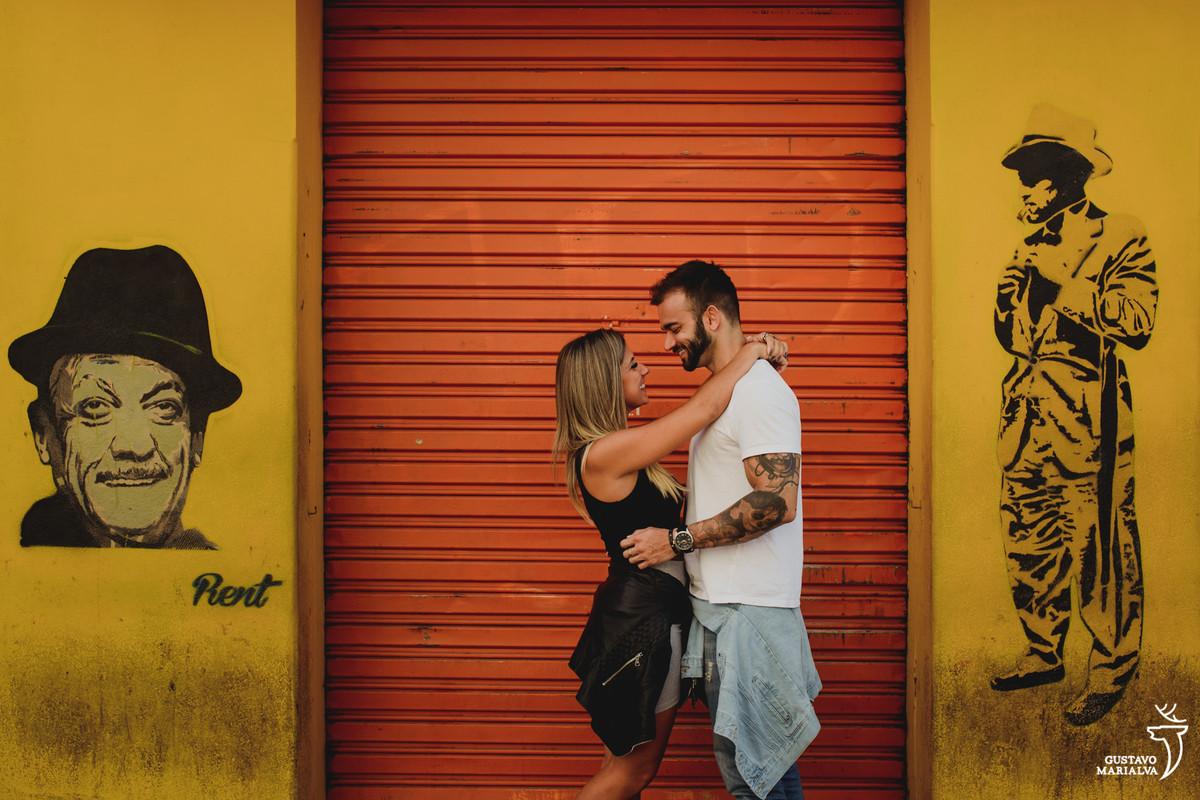 casal se abraça em frente a portão laranja durante book de casal realizado em curitiba