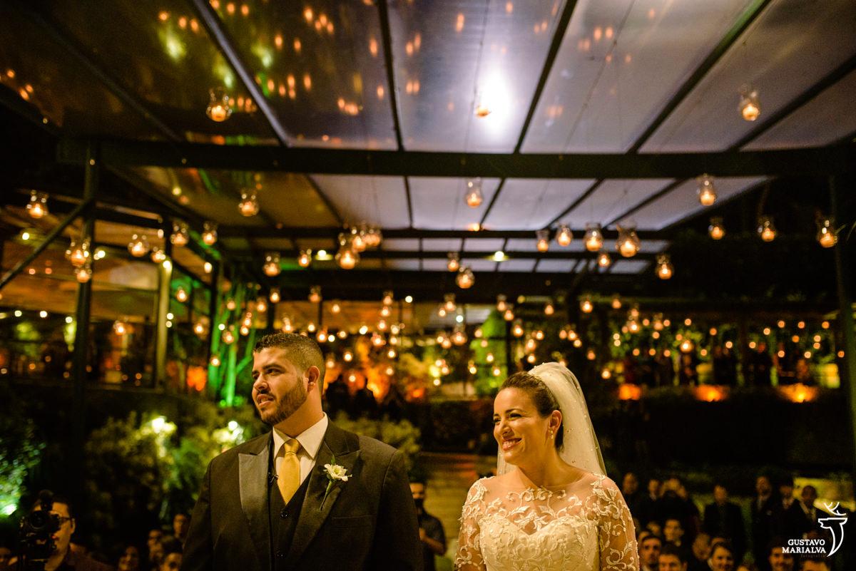 noivos sorriem com o sermão do padre durante a cerimônia de casamento na casa das canoas
