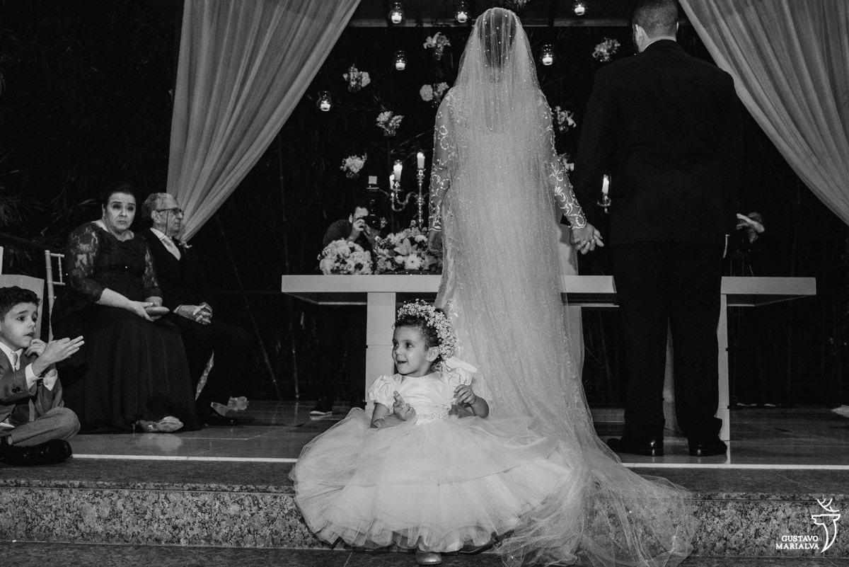 daminha sorrindo sentam em cima do vestido carol hungria da noiva durante a cerimônia de casamento