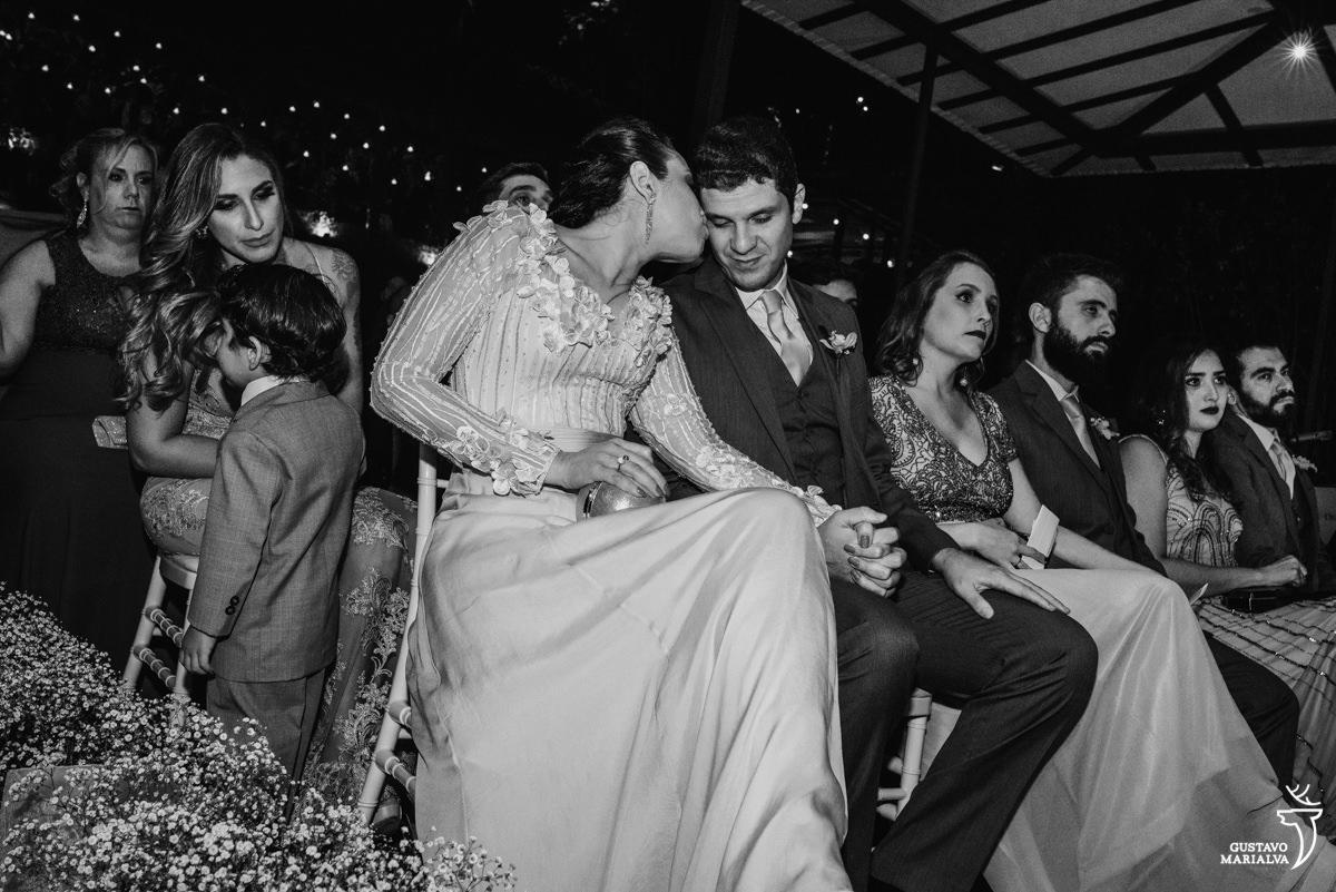 casal se beija de mãos dadas durante a cerimônia de casamento e menino brinca ao fundo