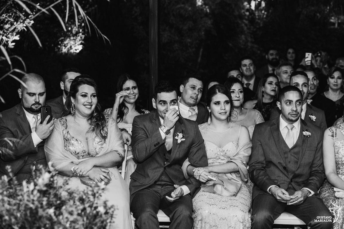 convidados choram, passando o lenço nos olhos e sorrindo durante a cerimônia de casamento