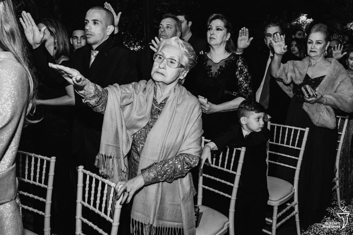 convidados e senhora esticam o braço para abençoarem o casal enquanto menino brinca