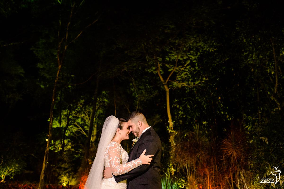 noivos posam abraçados com floresta ao fundo