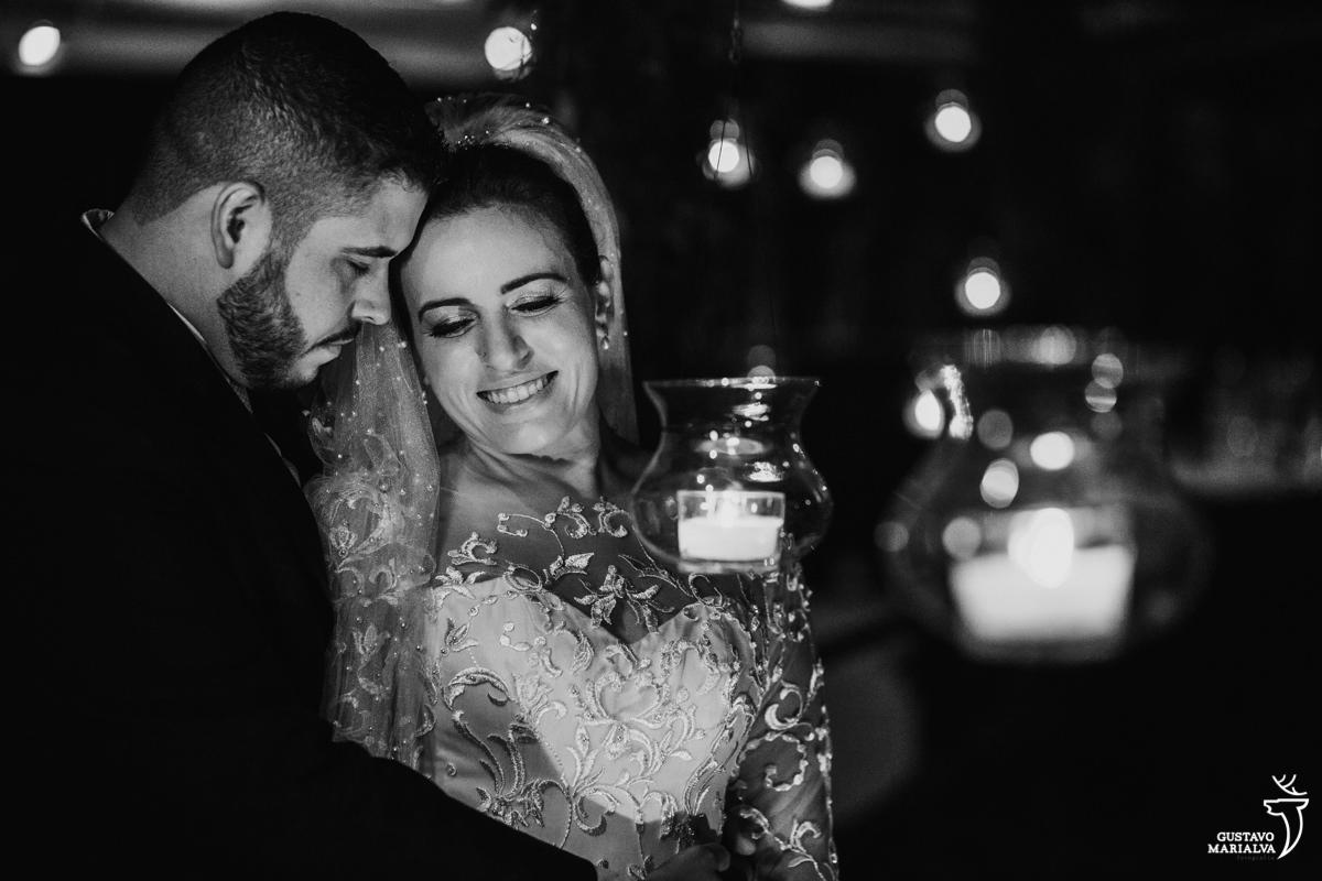 noivos posam abraçados envolvidos por velas acesas