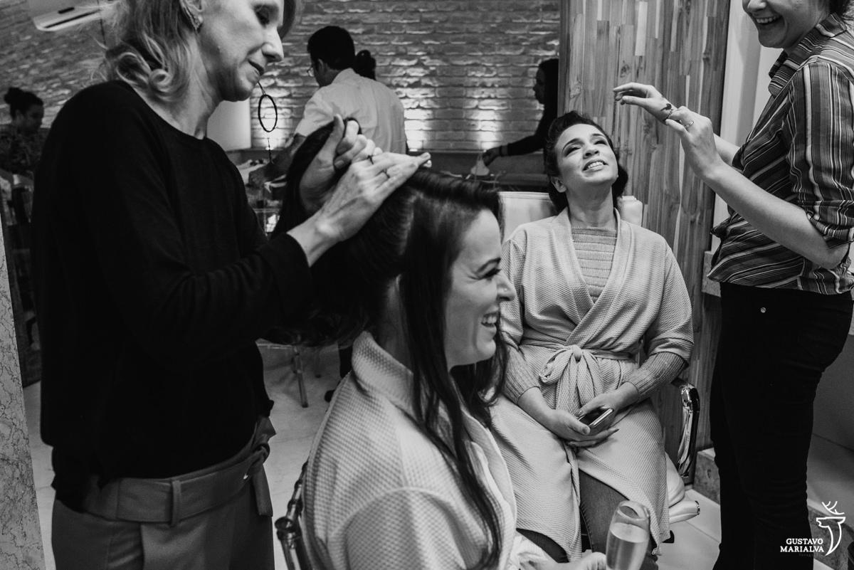 noiva sorrindo ao fazer o cabelo e irmã da noiva fazendo careta durante o making of do casamento