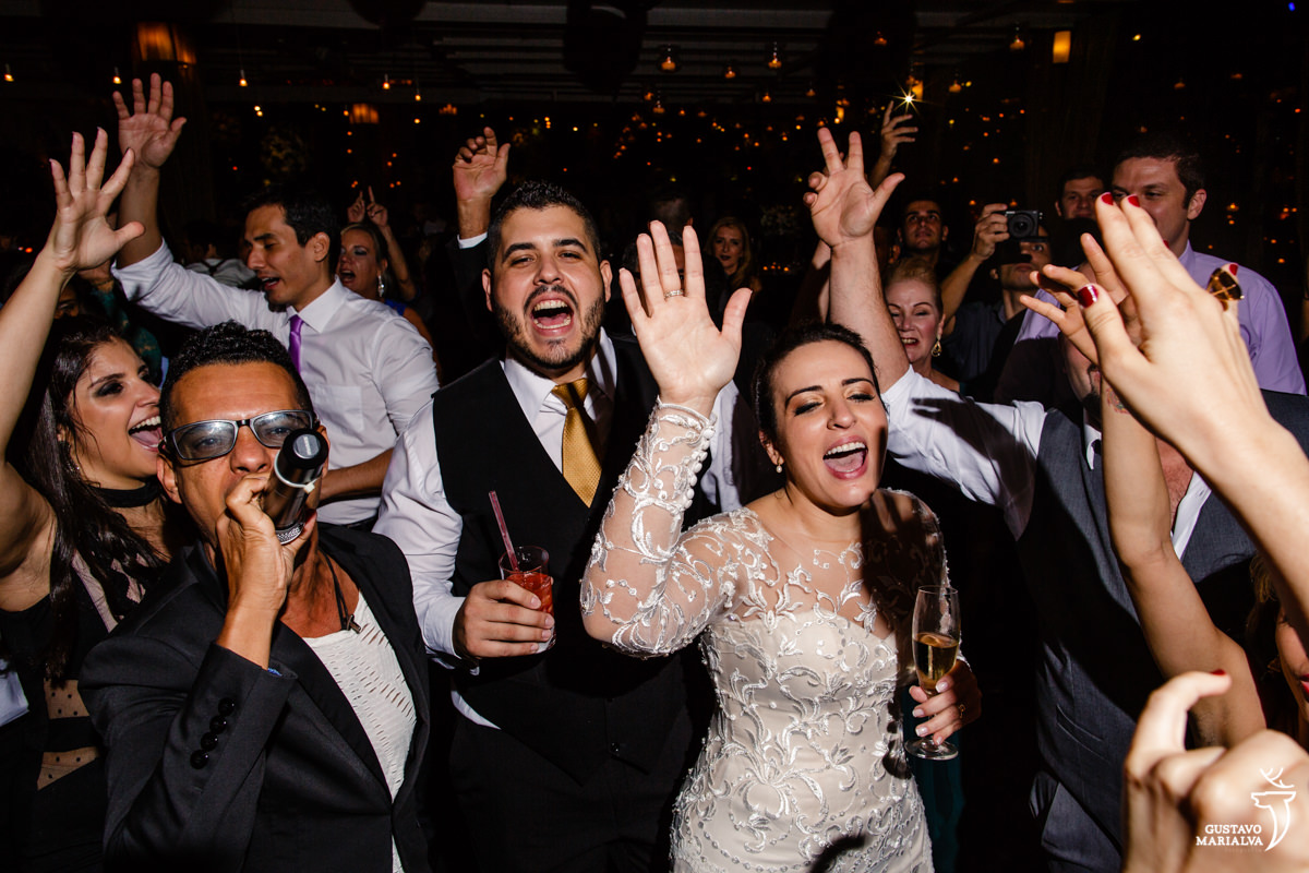 noivos dançam com as mãos para cima enquanto mc andinho canta no microfone