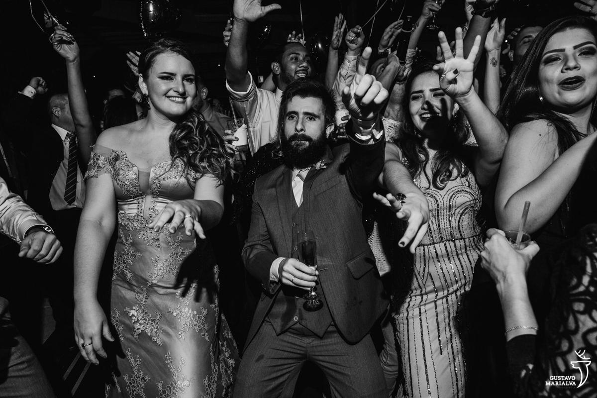 convidados dançam e sorriem com as mãos para cima