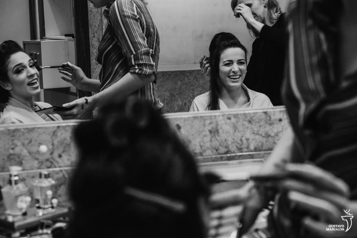 noiva e irmão sorriem ao se maquiarem para o casamento