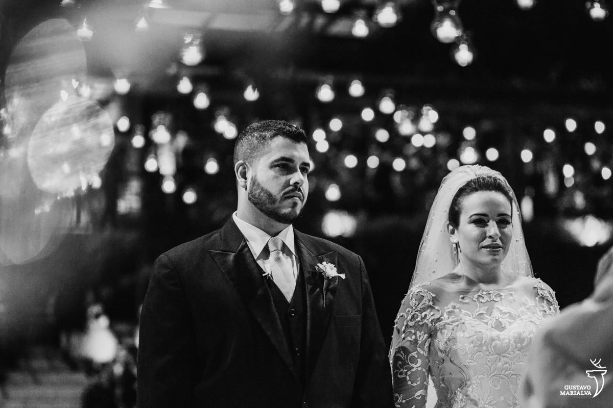 Noivos emocionados prestam atenção na cerimônia de casamento com velas desfocadas ao fundo