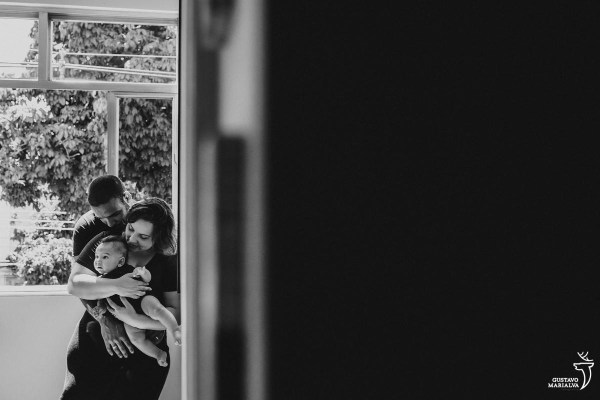 pais se abraçam encostados na parede e seguram o filho