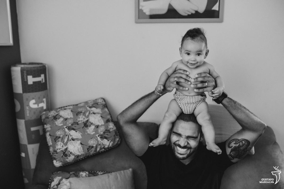 pai coloca o filho sentado em sua cabeça que sorri
