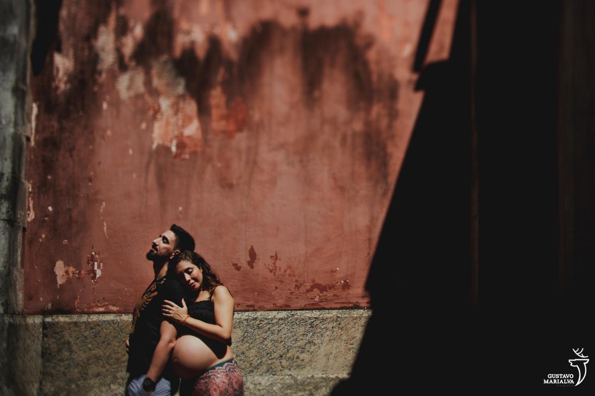 mulher grávida abraça homem por trás