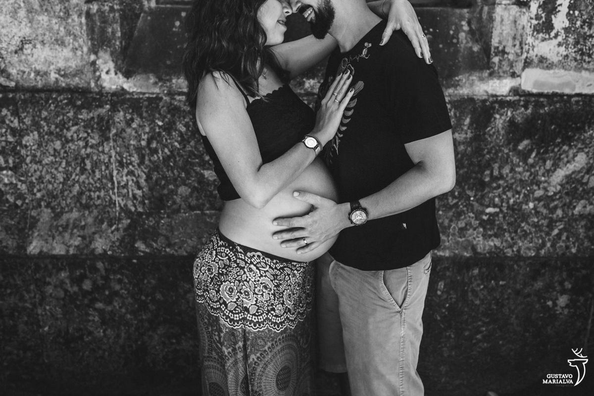 casal de grávidos se abraça sorrindo