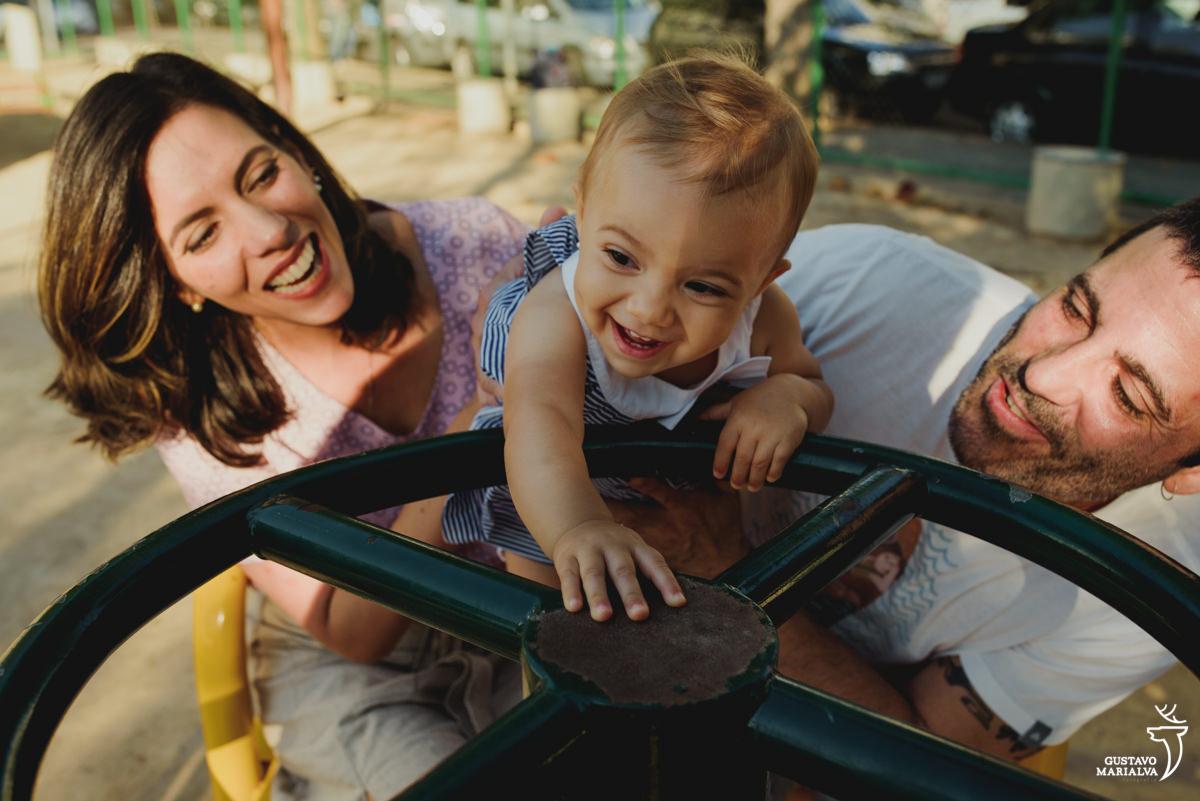 pais brincam com a filha na roda gigante durante ensaio de família realizado na urca