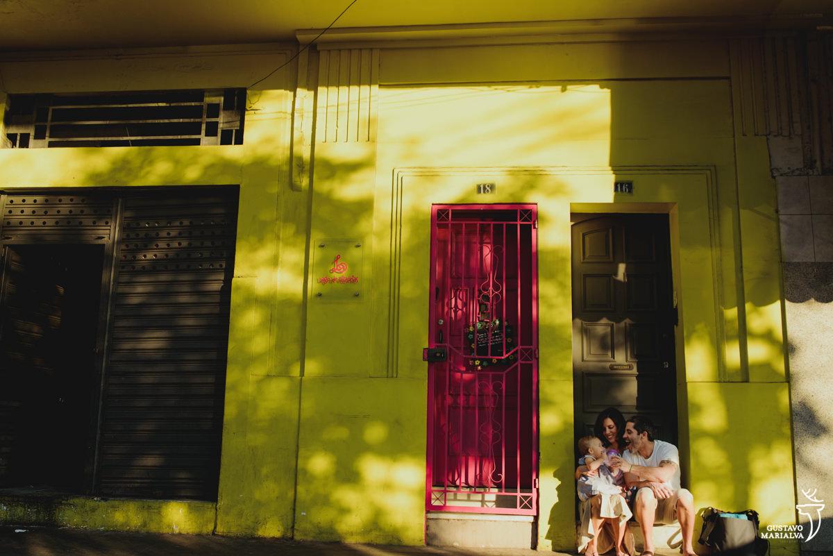 Pais sentam em frente a parede amarela e brincam com a filha no colo