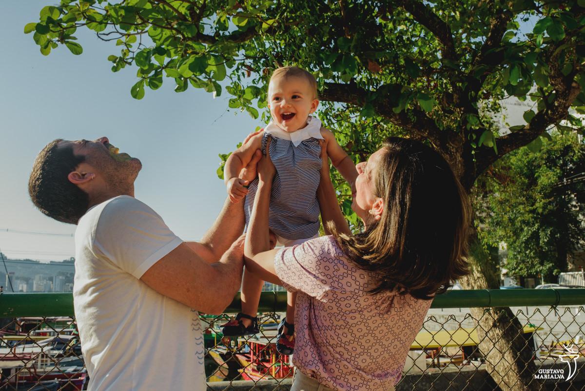 mãe joga a filha para o alto que sorri enquanto pai dá uma gargalhada
