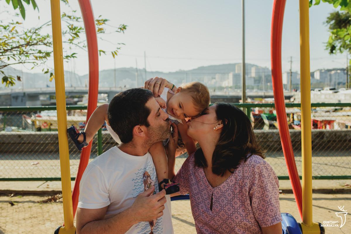 pais carregam a filha nas costas e dão um beijo