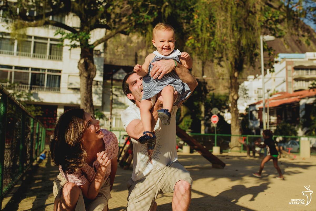 pai joga a filha para o alto e sorri e é observada pela mãe sorridente