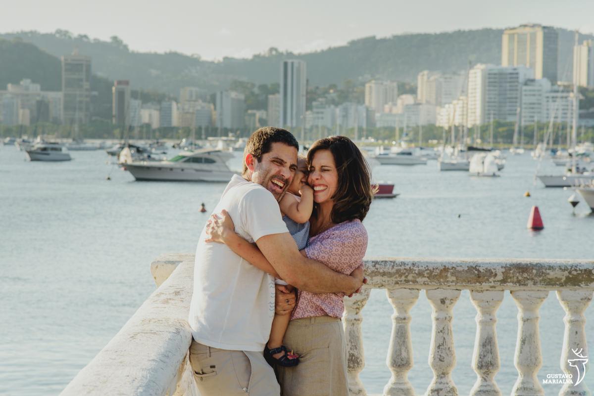 pais abraçam e espremem a filha durante ensaio de família realizado na urca