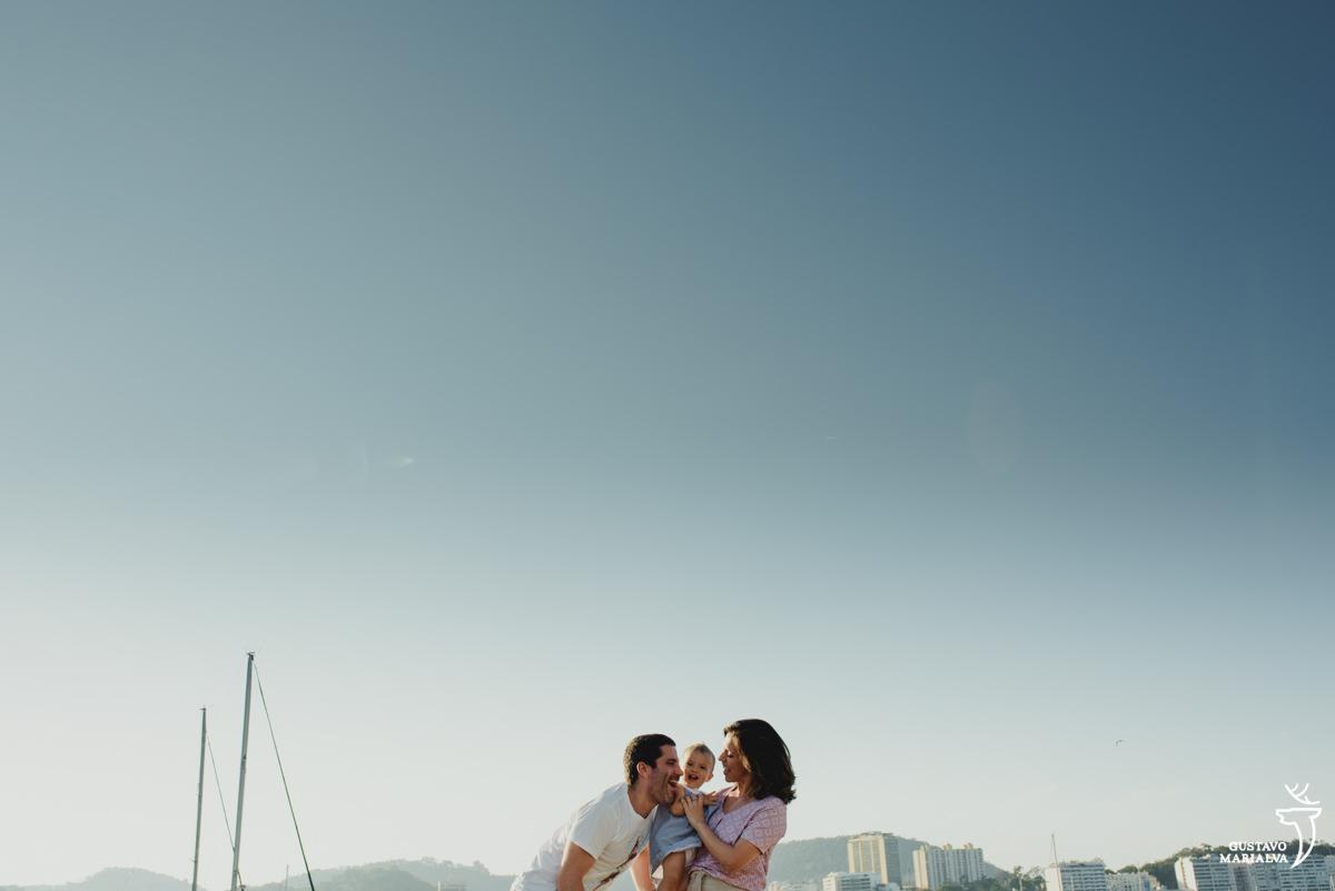 mãe segura a filha do colo enquanto o pai dá um beijo em sua bochecha