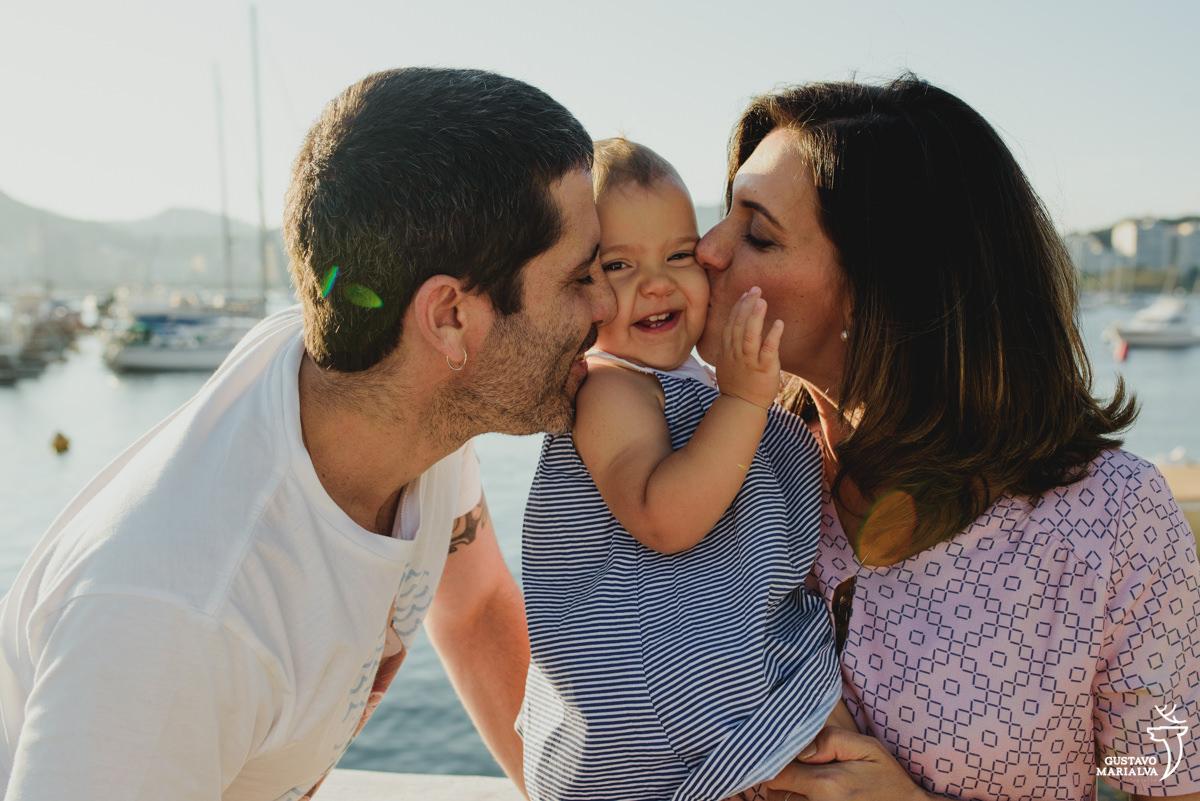 pais beijam a bochecha da filha que sorri