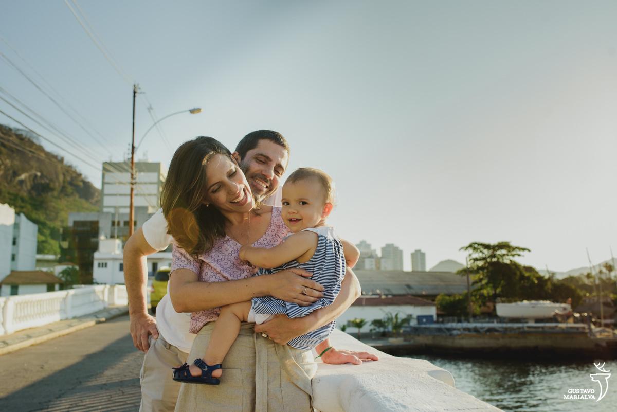 pais se abraçam e seguram a filha no colo que sorri para a câmera