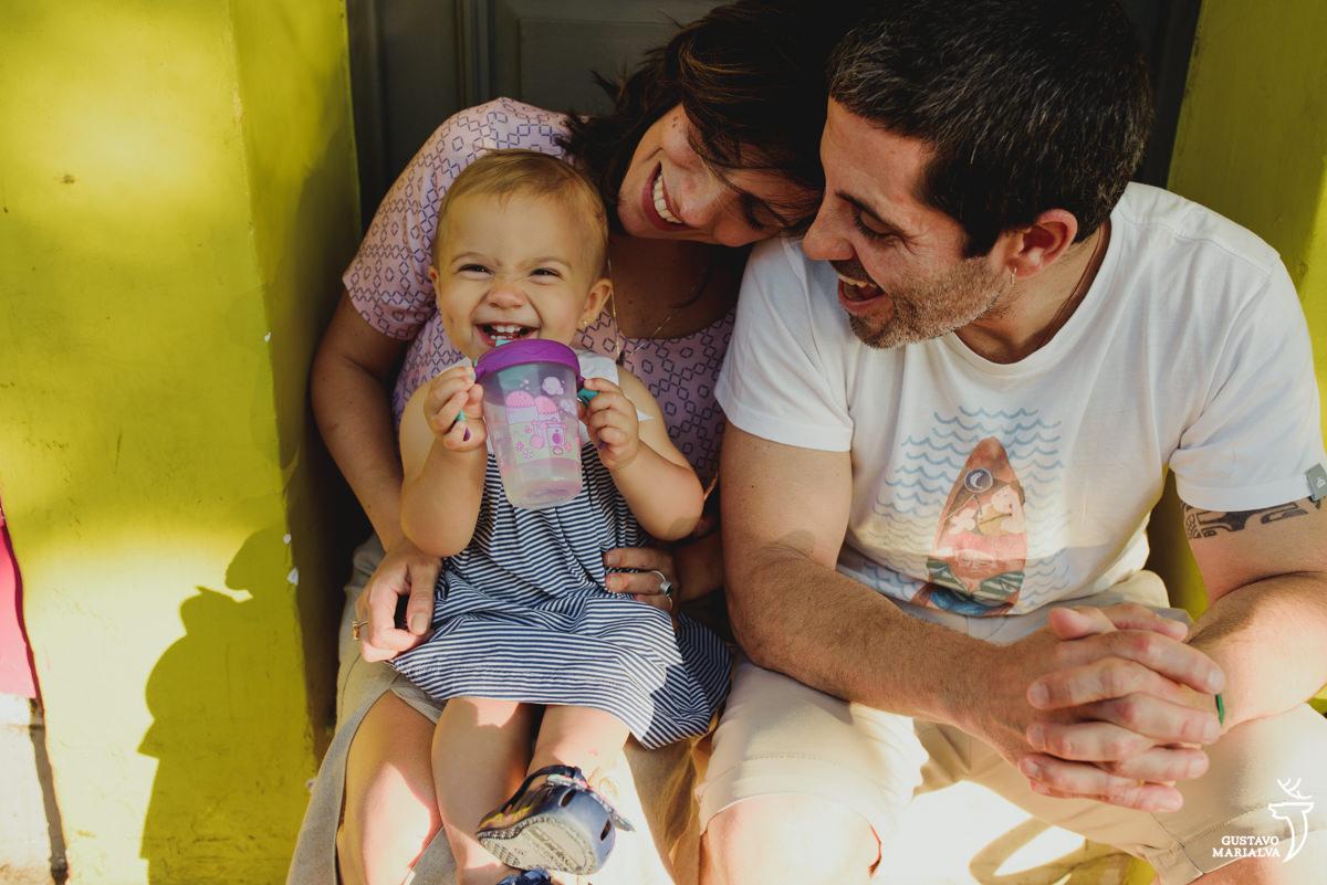 menina sorri segurando a garrafinha de água enquanto é observada pelos pais emocionados