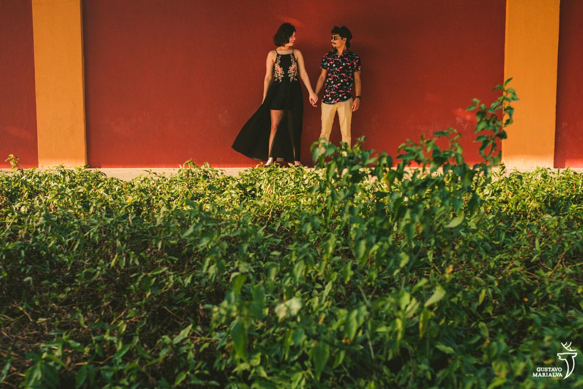 Casal olhando de mãos dadas com parede vermelha de fundo e chão de grama verde