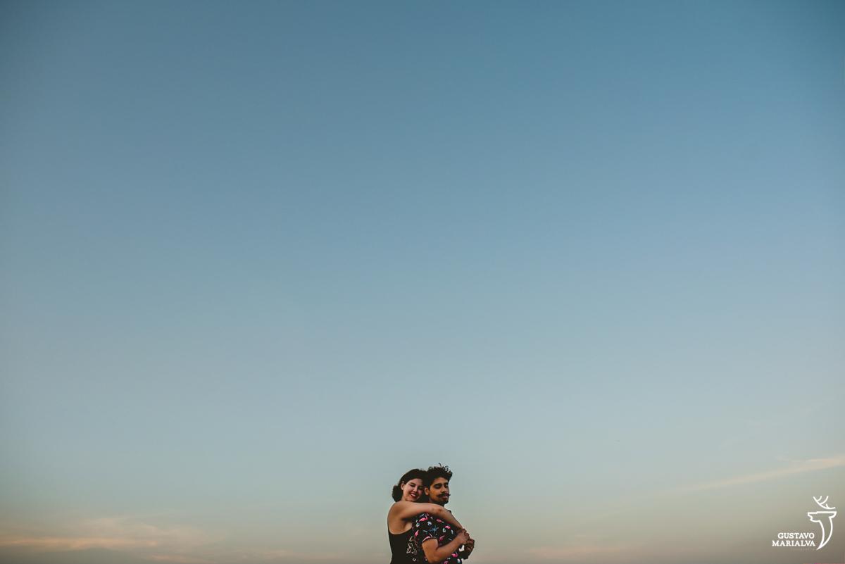 esposa abraça o marido por trás com o por de sol ao fundo