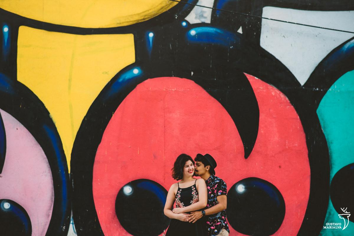 homem abraça a esposa por trás e dá um beijo em frente a parede de grafite