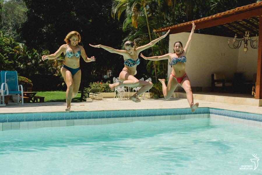 noiva, mãe e irmã pulando na piscina