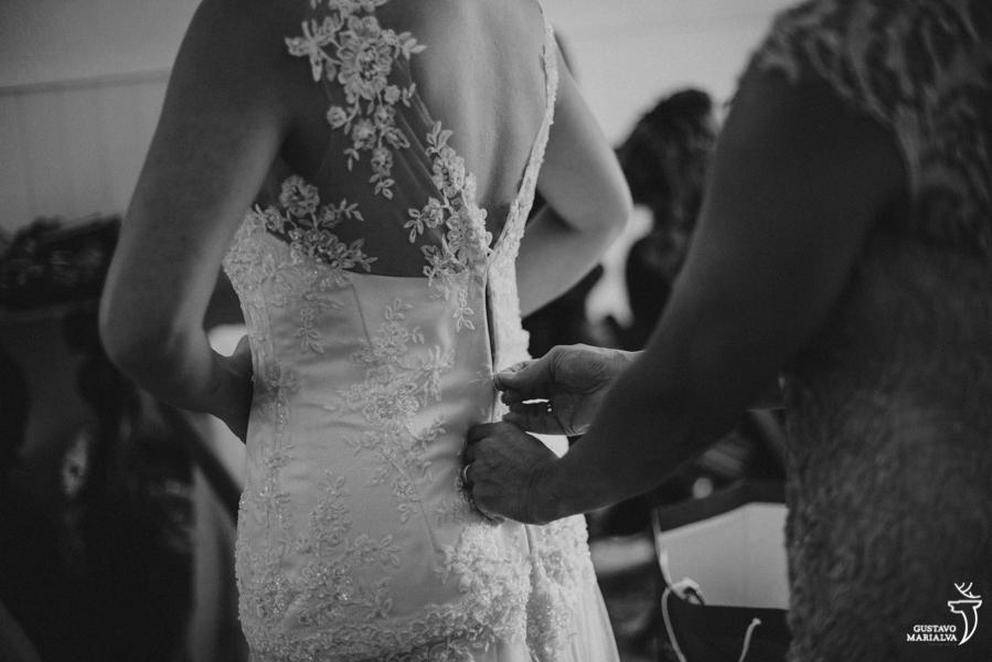 noiva fechando o vestido de noiva