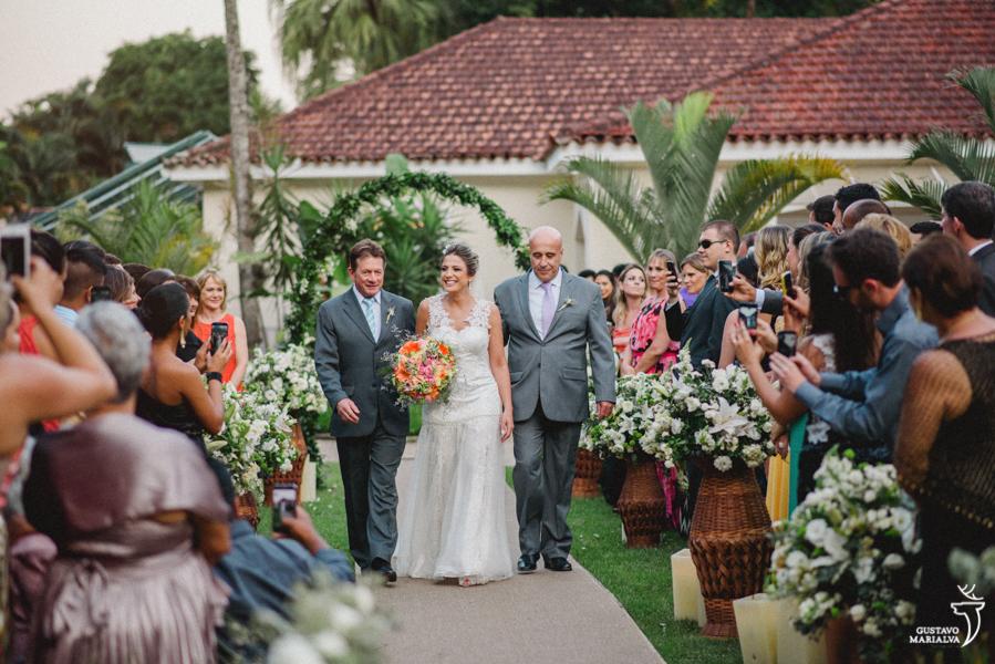 noiva entrando na cerimônia com pai e padrinho