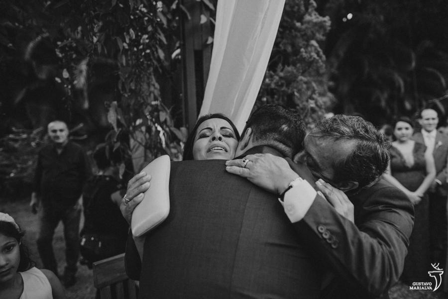 pais emocionados abraçando o noivo