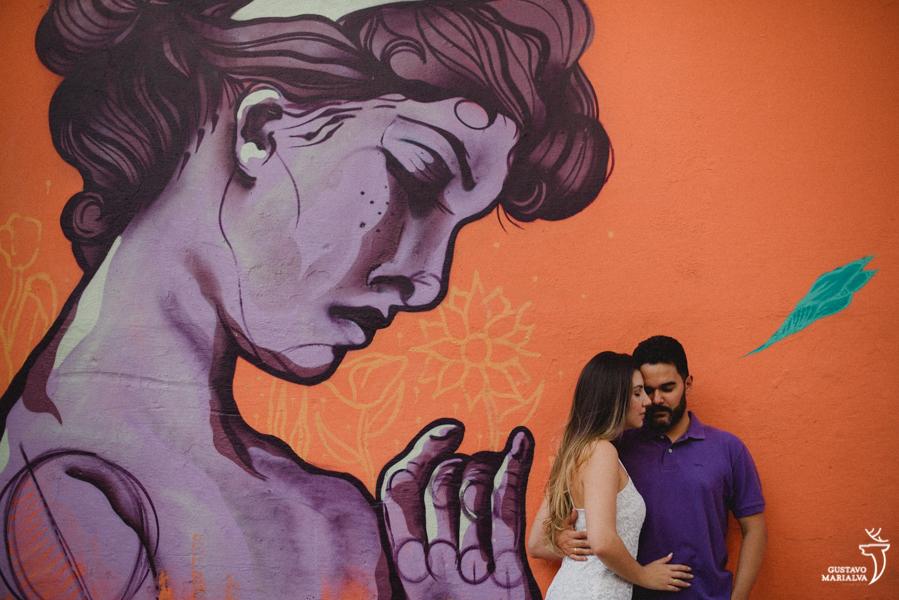 noivos namorando em frente a um grafite