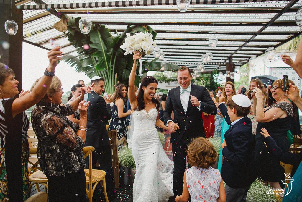 noivos saindo felizes da cerimônia de casamento