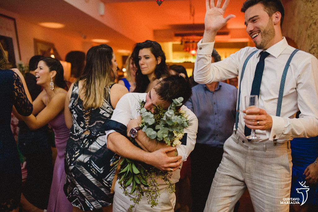 Amigo agarrando o buquê na festa de casamento